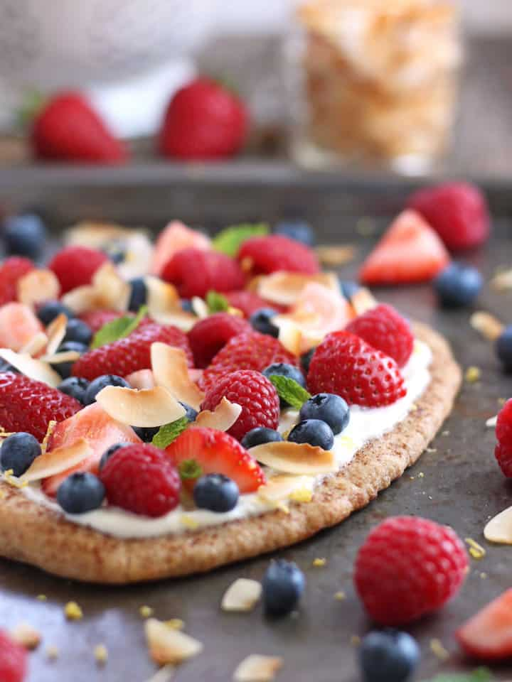Berries and toasted coconut on a ricotta topped flatbread.