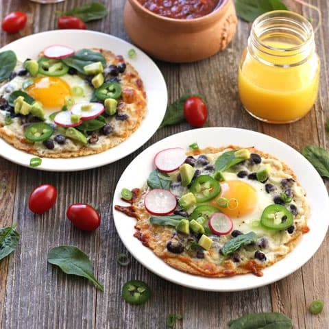 Two breakfast tostadas on a table with a bowl of salsa and glass of orange juice.