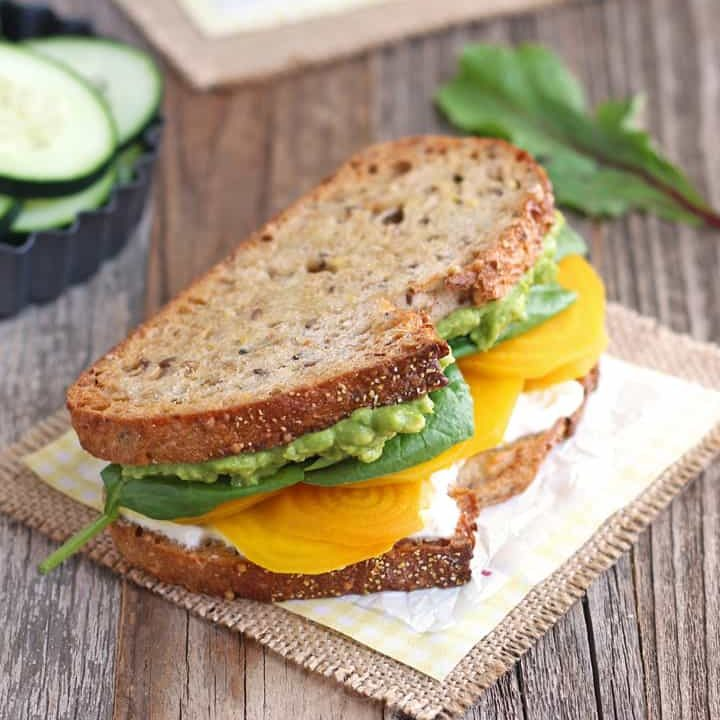 Golden beet and avocado sandwich on a piece of parchment.