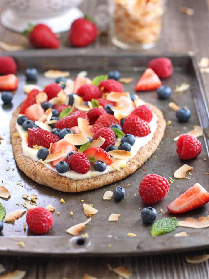 A fruity breakfast flatbread on a baking sheet with fresh berries and coconut.