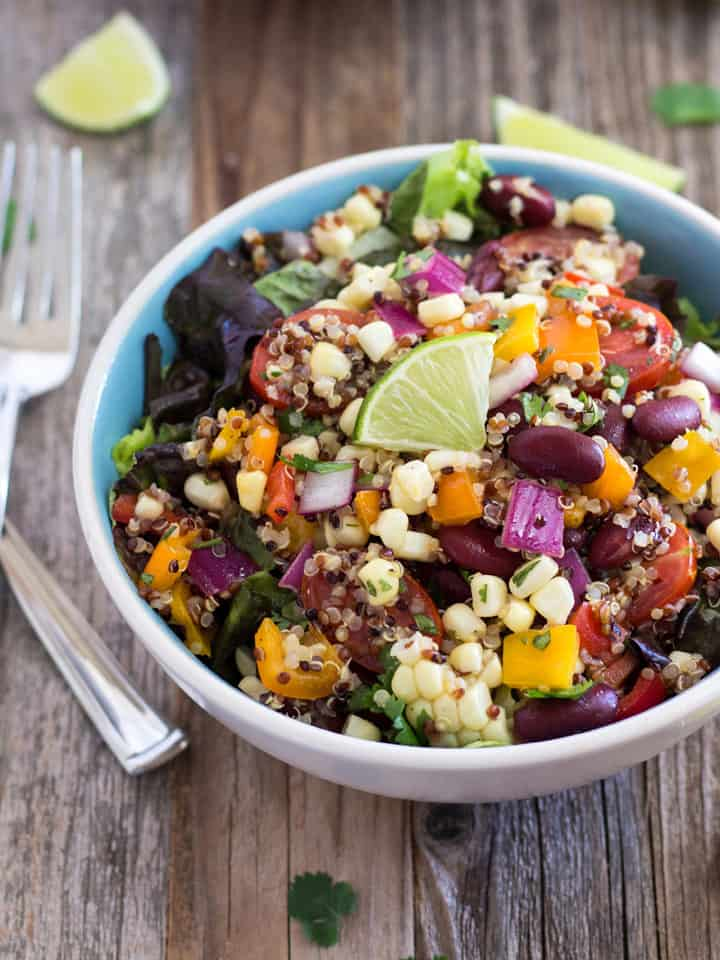 Blue bowl loaded with corn and quinoa salad.
