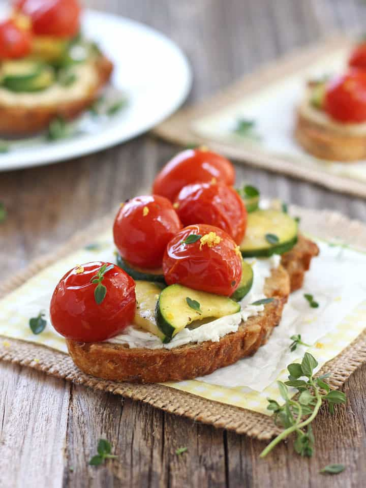 Juicy tomatoes on a goat cheese topped crostini on a wooden table.