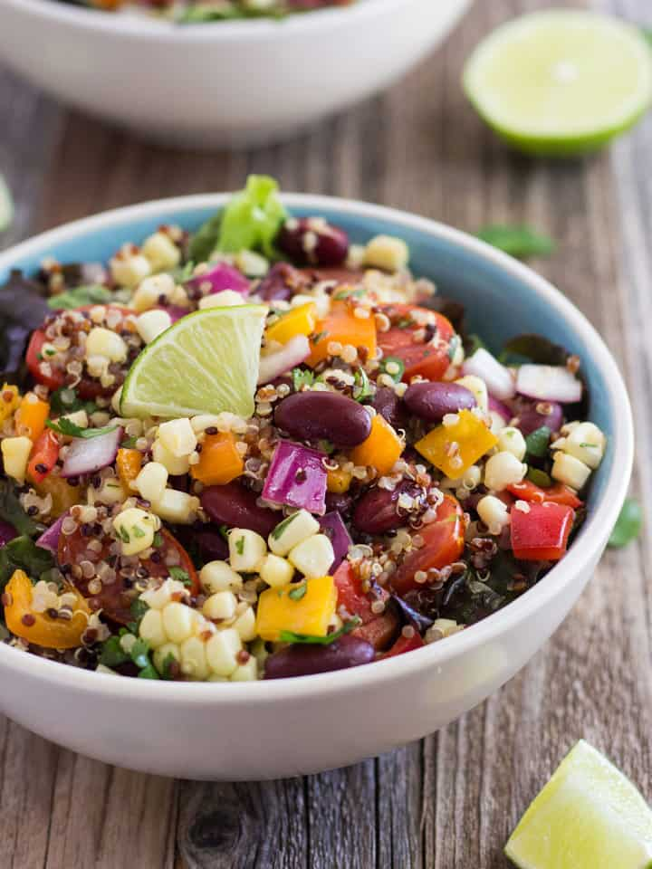 Close up of corn and quinoa salad topped with a lime wedge.
