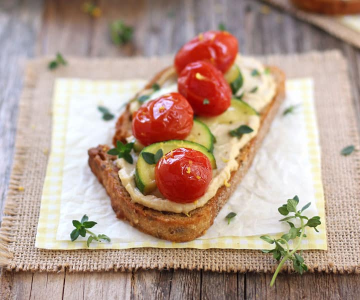 Hummus topped bread with juicy tomatoes and zucchini on a piece of white parchment.