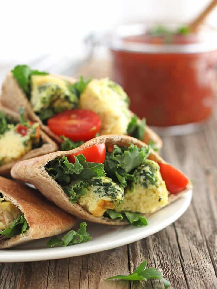 Toaster Oven Egg Muffins chopped up inside a pita with kale and sliced cherry tomatoes.