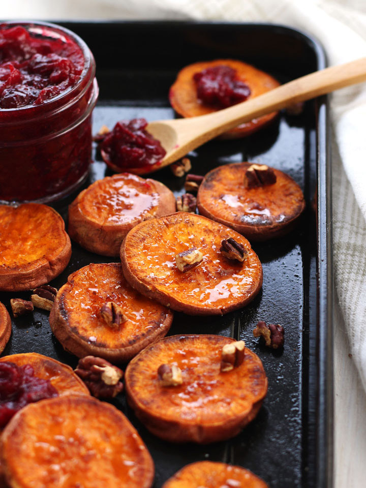 Roasted sweet potato rounds topped with pecans with a small jar of cranberry sauce.