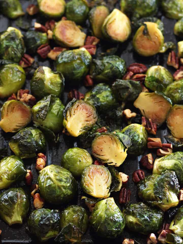 A pan of sticky sweet cooked Brussels sprouts with toasted pecans.