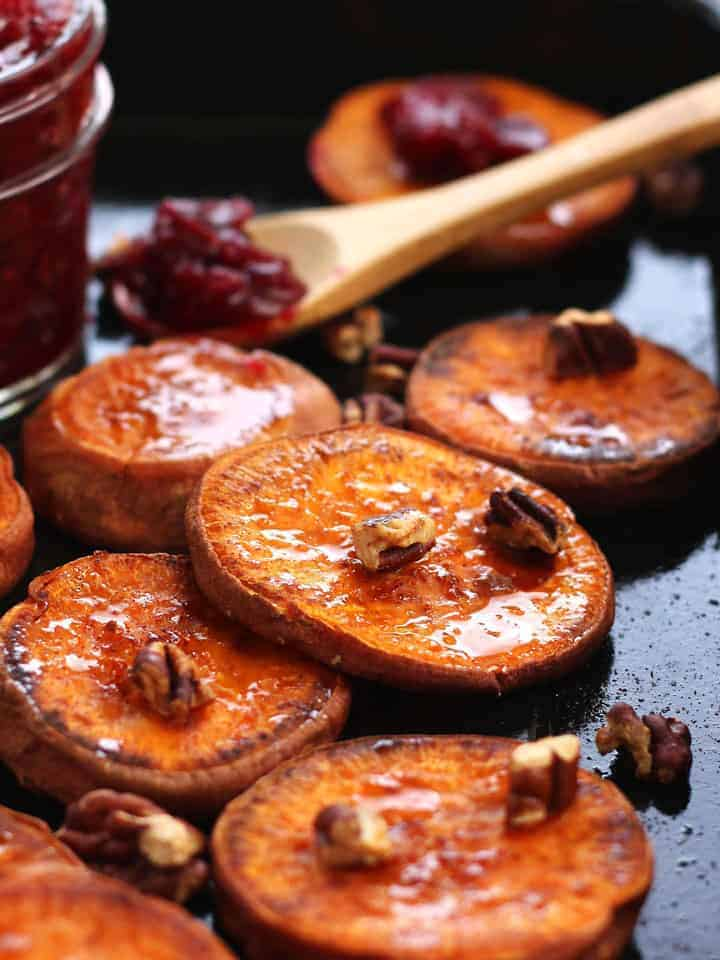 Roasted Sweet Potato Rounds on a baking sheet with pecans and cranberry sauce.