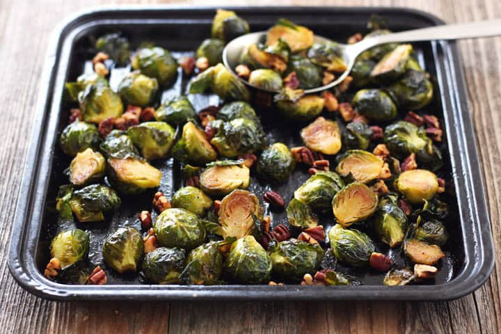 Cooked Brussels sprouts on a small sheet pan with a large metal spoon.
