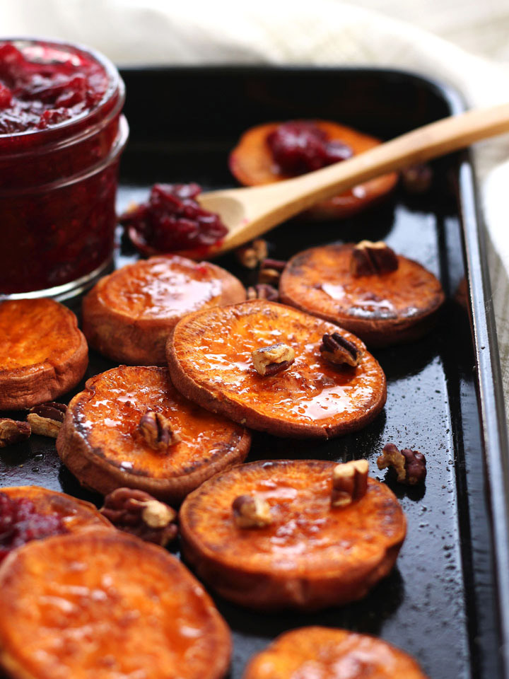 Baked sweet potato slices on a roasting pan with a jar of cranberry sauce.