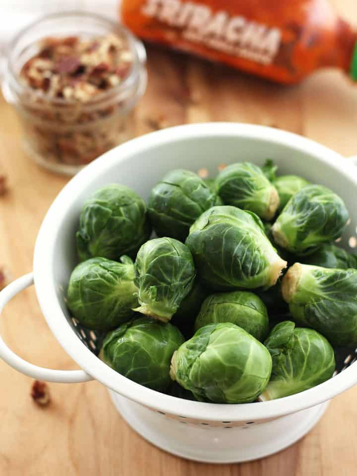 Fresh Brussels sprouts in a white colander on a cutting board.
