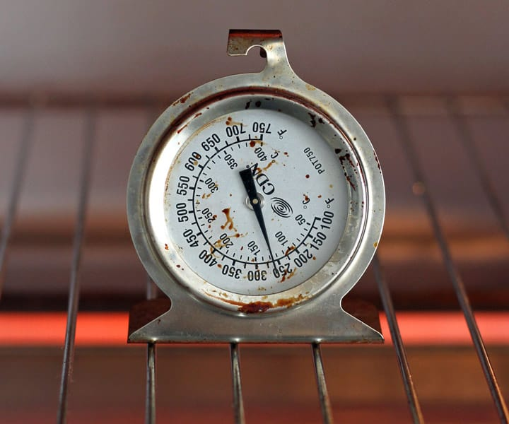 Closeup of oven thermometer on a cooking rack.