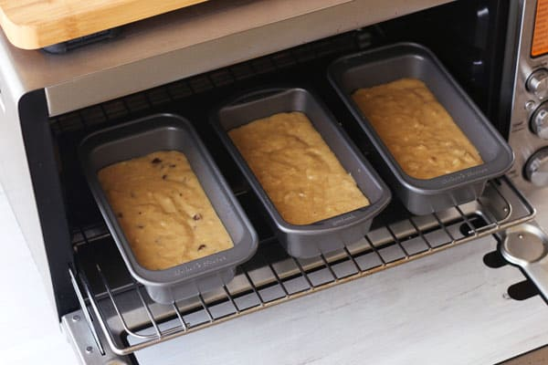 3 mini loaf pans full of batter inside of a toaster oven