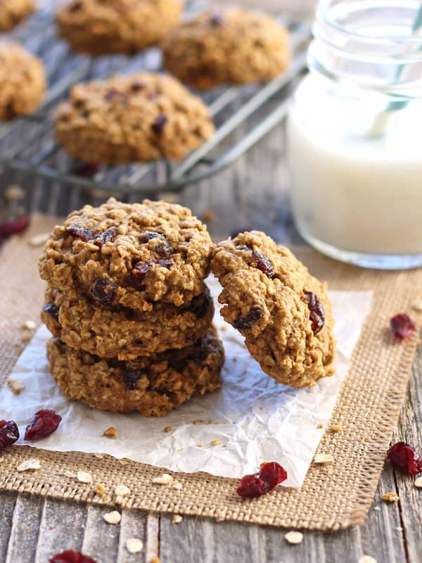A small stack of oatmeal cookies on a wooden table with a glass of milk.