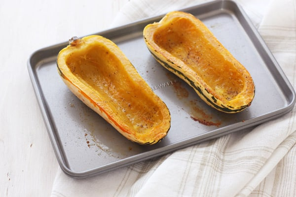 Cooked delicata squash boats on a toaster oven baking sheet.