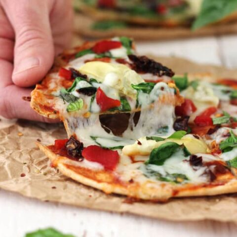 Tortilla Pizzas with Sundried Tomatoes and Spinach are the ultimate toaster oven treat. Just 15 minutes for cheesy veggie pizzas on a crispy tortilla crust.