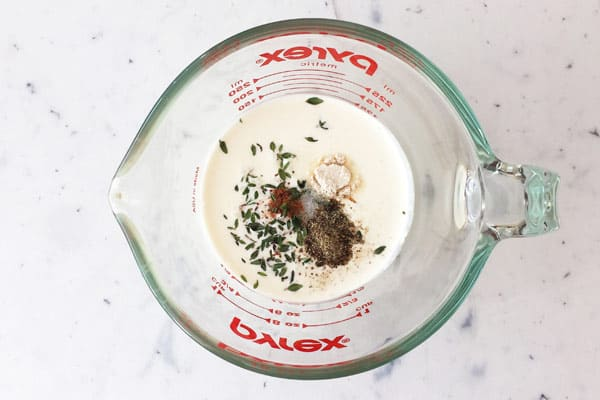 Cream in a measuring glass with seasonings and fresh thyme