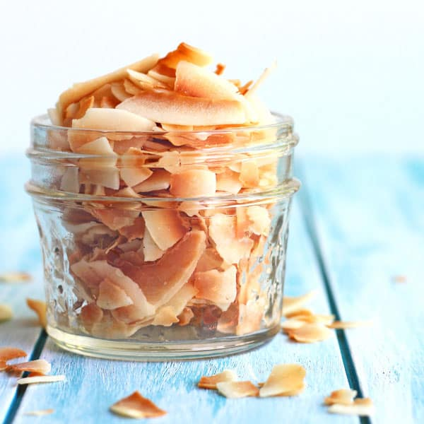 Toasted coconut flakes in a small glass mason jar.
