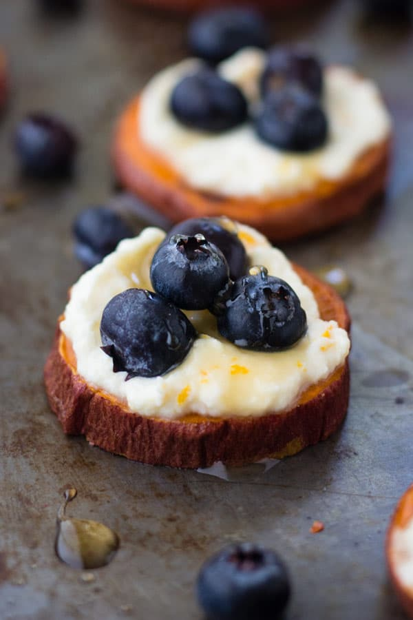 Closeup of sweet potato slice topped with ricotta and blueberries.