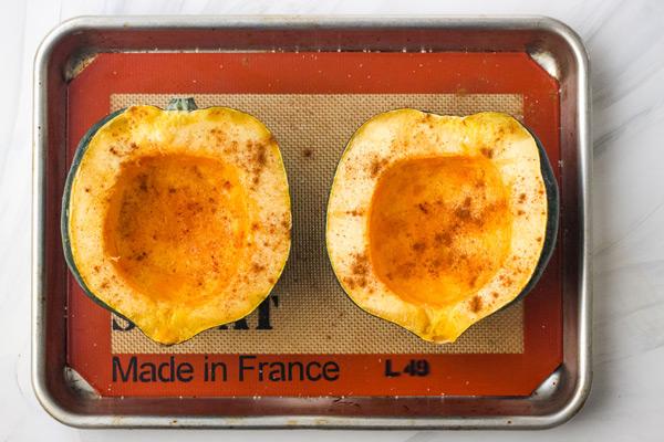 Oiled and seasoned squash halves on a quarter sheet pan.