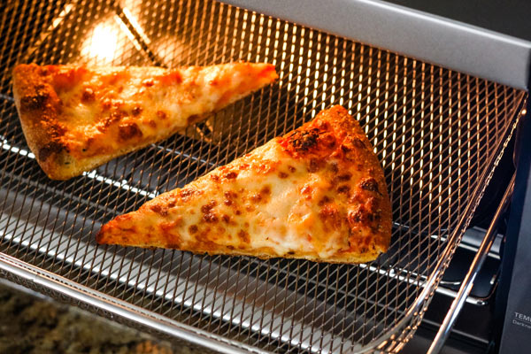 Cheese pizza slices in a metal basket inside a toaster oven.