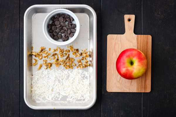 Shredded coconut, nuts and chocolate in a ramekin on a baking pan and an apple on a cutting board.