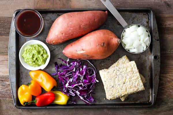 Tempeh Stuffed Sweet Potatoes ingredients on a baking pan.