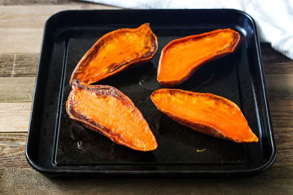 Baked sweet potato halves on a dark roasting pan.
