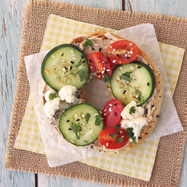 Toasted everything bagel with hummus, cucumbers and cauliflower.