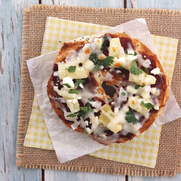 Toasted onion bagel with BBQ sauce, feta cheese, mozzarella cheese, onions and cilantro.