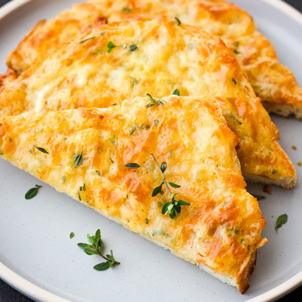Triangles of cheesy toast on a blue plate with fresh thyme leaves sprinkled on top.