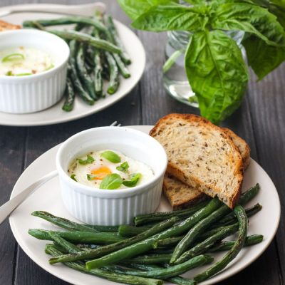 A white plate filled with green beans and a small ramekin with a baked egg.