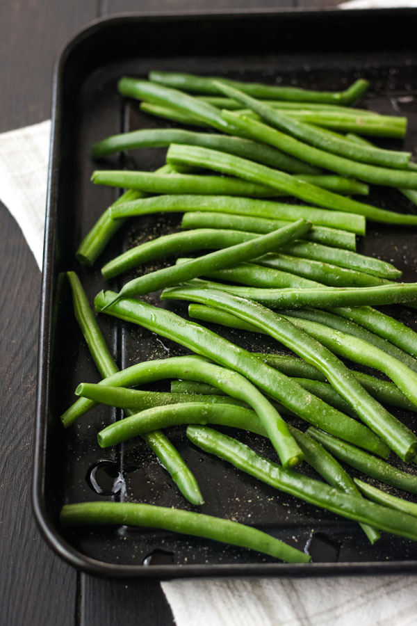 Fresh green beans on a black toaster oven baking sheet.