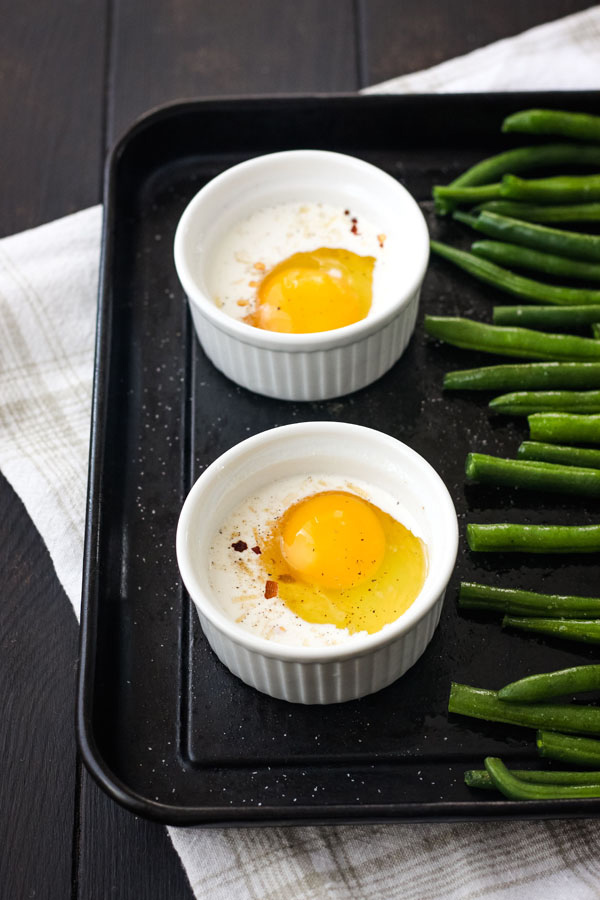 A toaster oven baking sheet with green beans and egg and cream filled ramekins.