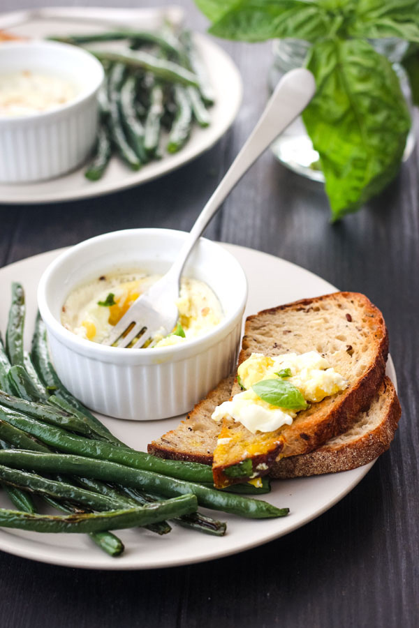 A plate of green beans and toast with creamy egg on top.