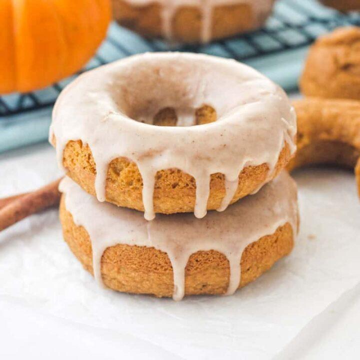 Glazed donuts stacked next to a mini pumpkin and cinnamon sticks.