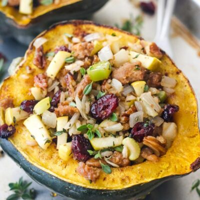 Close up of stuffed roasted squash with dried cranberries, pecans, and herbs.
