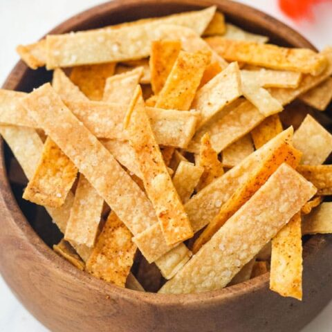 Tortilla strips in a small wooden bowl.