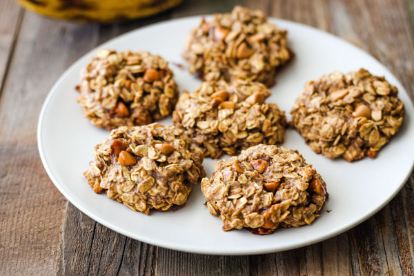 Banana oatmeal cookies on a white plate on a wood table.