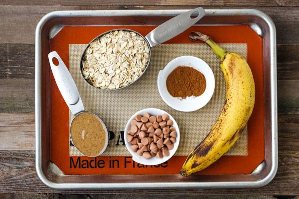 Oats, almond butter, cinnamon, a banana, and butterscotch chips on a baking sheet.