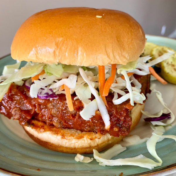 Meatloaf sandwich with slaw mix on a brioche bun.