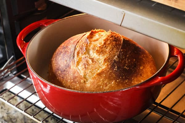 Small bread in dutch oven inside a countertop oven.