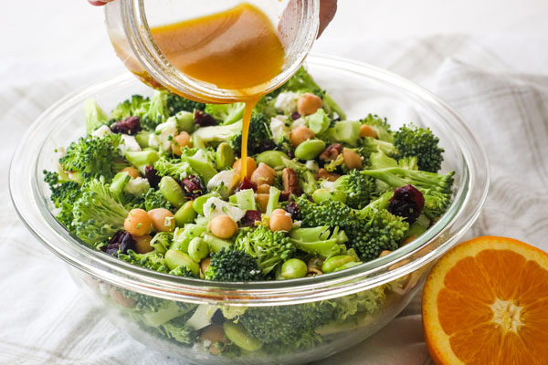 Hand pouring citrus vinaigrette from a mason jar over a bowl of broccoli salad.