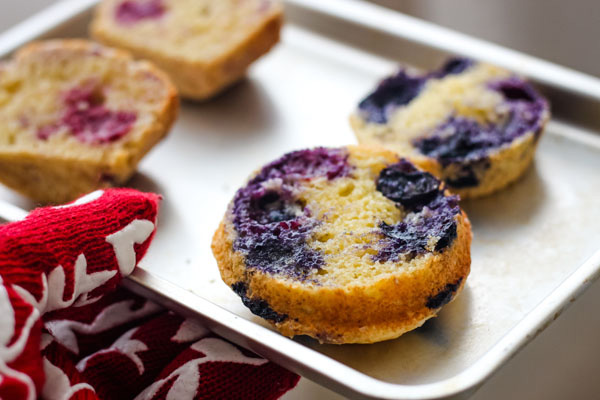 Buttery toasted blueberry muffin halves on a baking sheet.