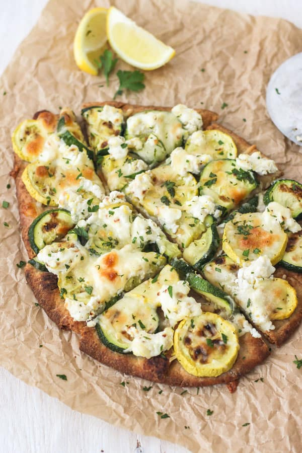 Broiled Zucchini and Lemon Ricotta Flatbread Sliced Into Pieces With Lemon Wedges