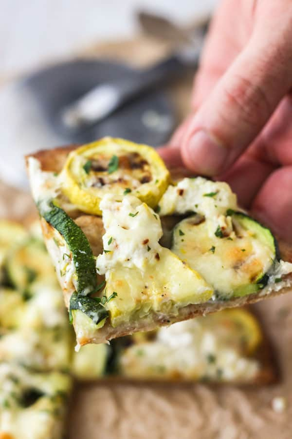 Hand holding slice of zucchini and lemon flatbread