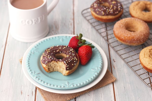 Nutella frosted baked buttermilk donut with sprinkles on a blue plate with strawberries.