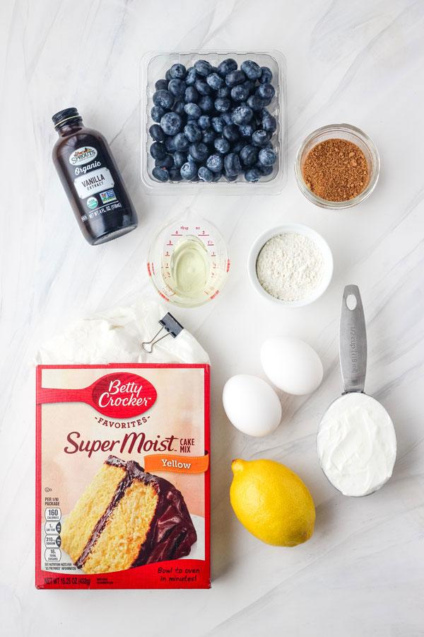 Boxed cake mix, fresh blueberries, eggs, yogurt and lemon on a table.