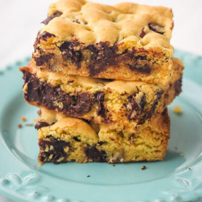 3 cookie bars stacked on a blue plate.