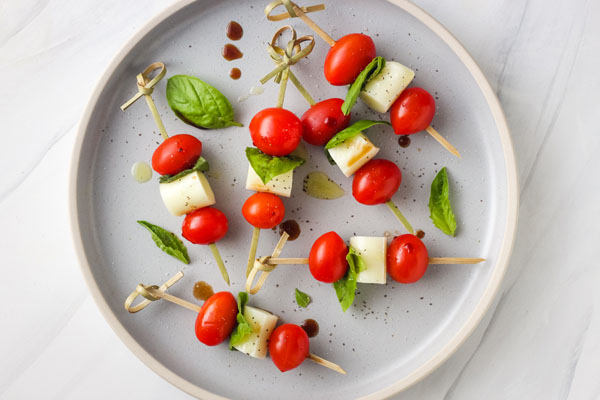 Caprese Skewers on a blue plate.